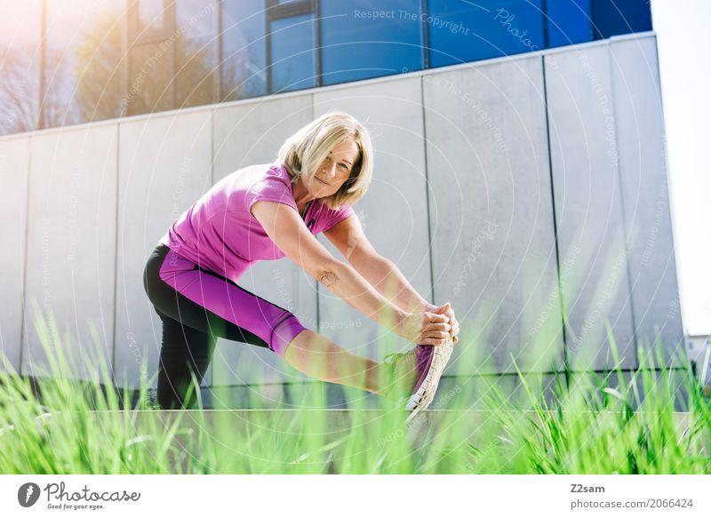 Rentnerin beim Stretching Freizeit & Hobby Sport Fitness Sport-Training Yoga Frau Erwachsene Weiblicher Senior 45-60 Jahre Sträucher Stadt Turnschuh blond