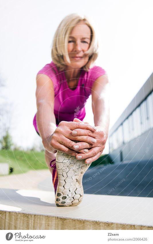 Rentnerin beim Stretching Lifestyle elegant Stil Freizeit & Hobby Sport Fitness Sport-Training Yoga Weiblicher Senior Frau Hand Fuß 60 und älter Stadt blond