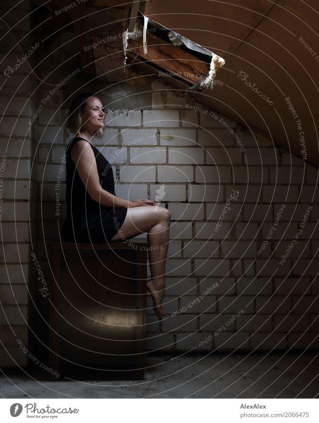 Junge Frau sitzt barfuß auf dem Dachboden auf einem Schrank vor einem Oberlicht exotisch schön Jugendliche Beine Fuß 18-30 Jahre Erwachsene Haus Dachschräge