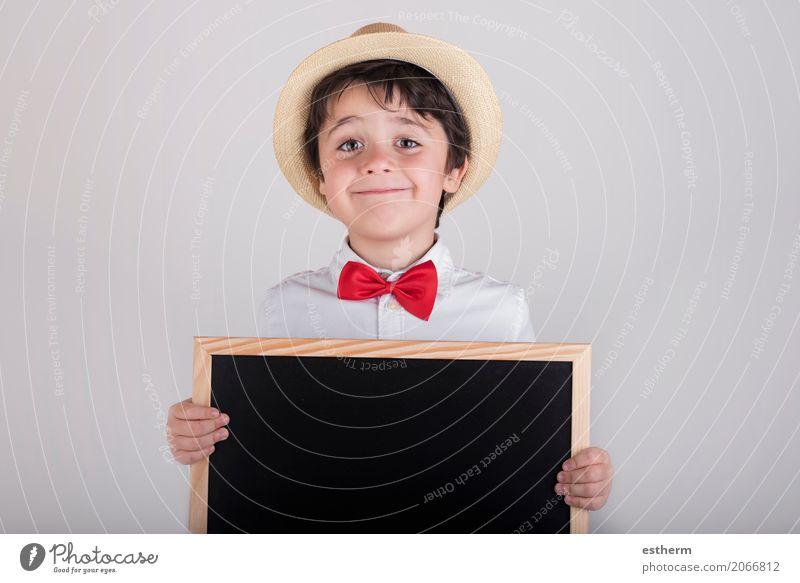 lächelndes Kind, das eine Tafel hält Lifestyle Freude Schulkind Mensch maskulin Kleinkind Junge 1 3-8 Jahre Kindheit Krawatte Hut festhalten Lächeln schreiben
