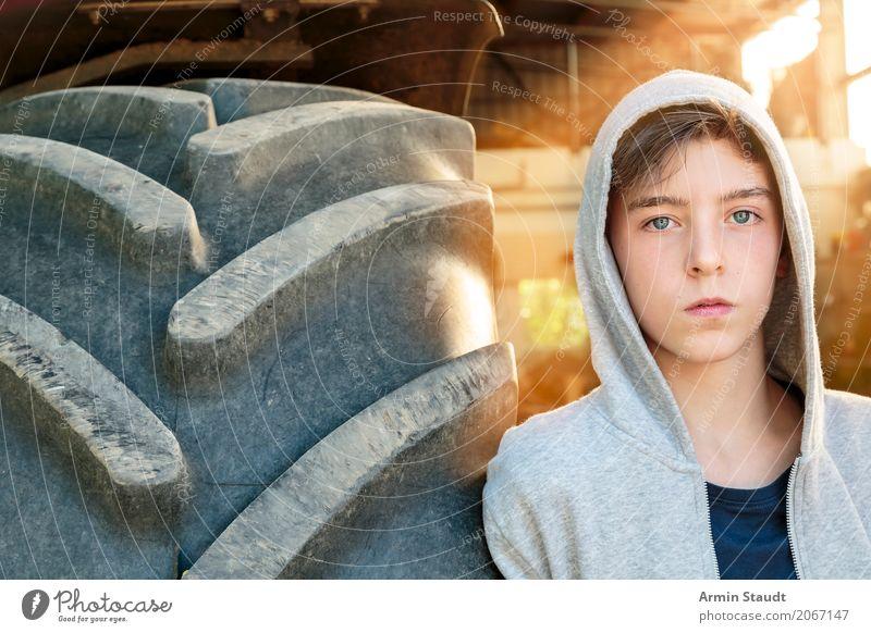 Porträt eines jungen Mannes der an einem Tracktorreifen lehnt Lifestyle Stil schön ruhig Sommer Mensch maskulin Junger Mann Jugendliche 1 13-18 Jahre Traktor