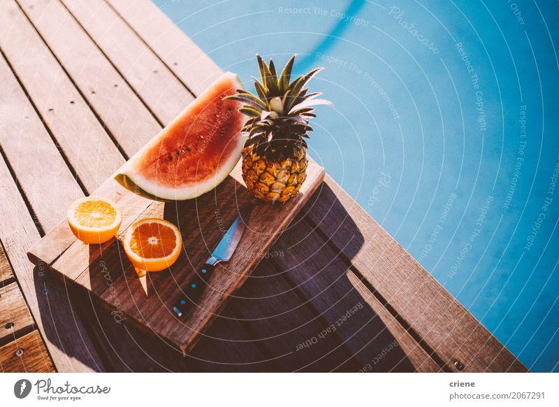 Platte mit tropischen Früchten neben Swimmingpool Lebensmittel Frucht Orange Ernährung Essen Teller Lifestyle Schwimmbad Schwimmen & Baden Freizeit & Hobby