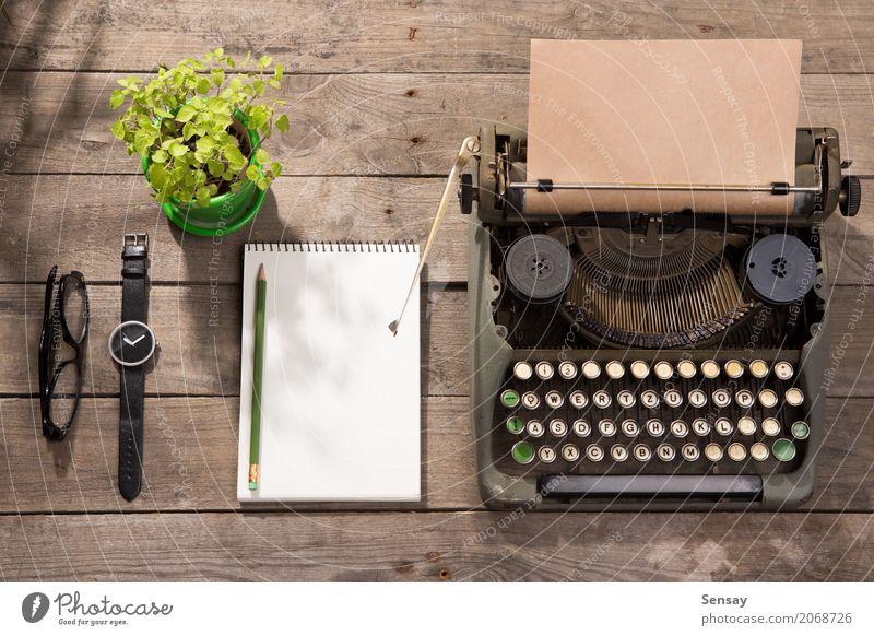 Vintage Schreibmaschine auf dem alten Schreibtisch aus Holz Pflanze grün Textfreiraum Büro retro Tisch Buch Papier beobachten Information Kaffee schreiben
