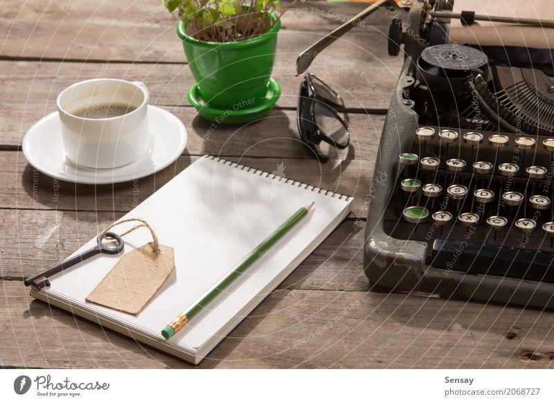 Vintage Schreibmaschine auf dem alten Schreibtisch aus Holz Pflanze grün Textfreiraum Büro retro Tisch Buch Papier Information Kaffee schreiben Spuren Tee