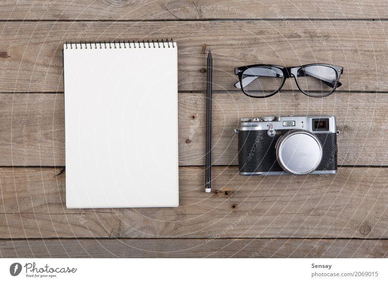 Notizblock, Gläser und Kamera auf dem hölzernen Schreibtisch Ferien & Urlaub & Reisen alt weiß schwarz Holz Business oben Textfreiraum Büro retro Tisch