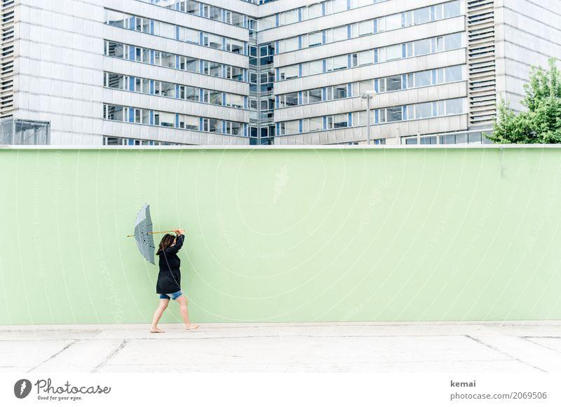 Frau mit Regenschirm vor grüner Wand, im Hintergrund Hochhäuser Lifestyle Leben harmonisch Freizeit & Hobby Ausflug Freiheit Mensch feminin Erwachsene 1