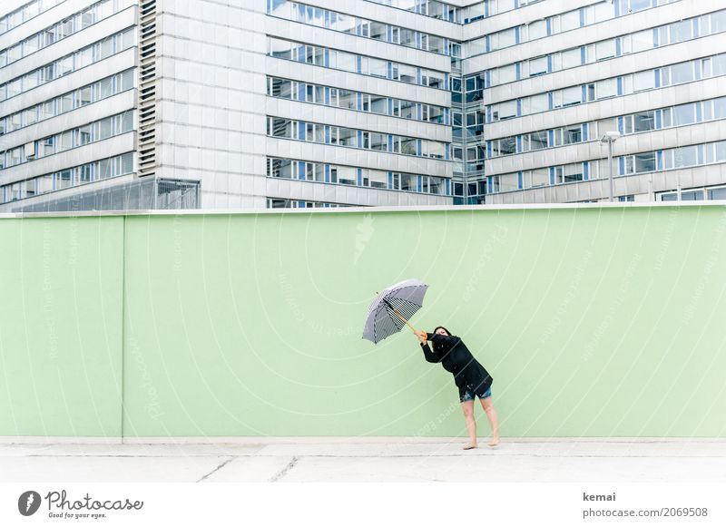 Frau mit Regenschirm vor grüner Wand, im Hintergrund Hochhäuser Freude Freizeit & Hobby Ferien & Urlaub & Reisen Ausflug Abenteuer Freiheit Städtereise Mensch