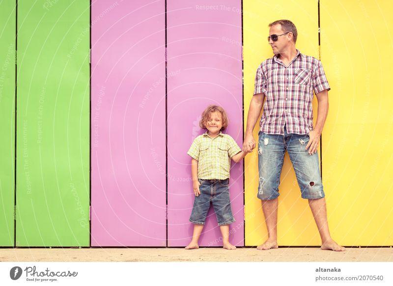 Vater und Sohn entspannen sich in der Nähe des Hauses am Tag. Sie stehen in der Nähe sind die bunten Wand. Konzept der freundlichen Familie. Lifestyle Freude