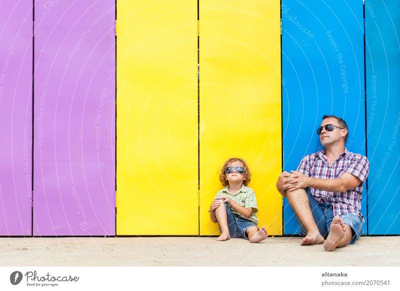Vater und Sohn entspannen in der Nähe des Hauses in der Tageszeit. Sie sitzen in der Nähe sind die bunten Wand. Konzept der freundlichen Familie. Lifestyle