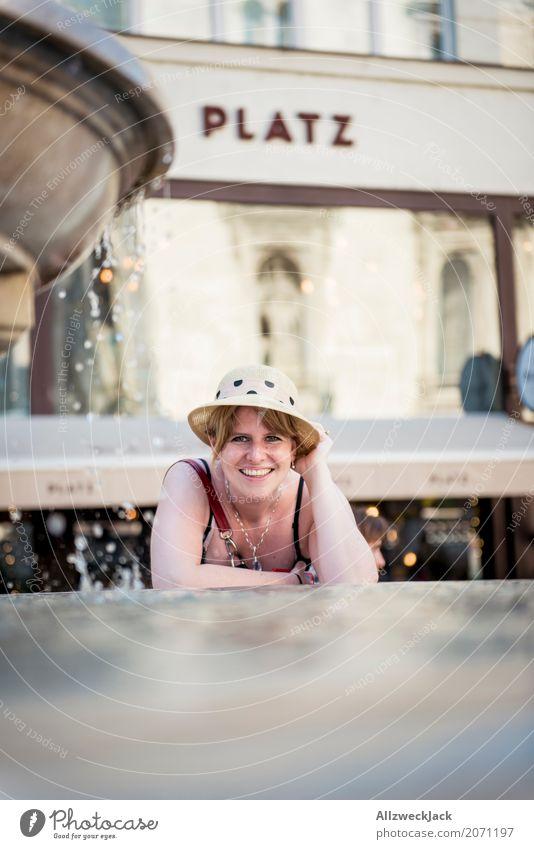 Portrait mit Hut am Brunnen 3 Frau Ferien & Urlaub & Reisen Freude Erwachsene Leben feminin lachen Glück Zusammensein blond Lächeln Fröhlichkeit Platz