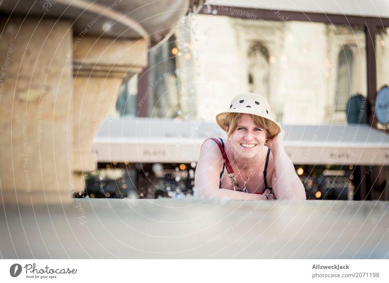 Portrait mit Hut am Brunnen 2 Farbfoto Außenaufnahme Tag Porträt Blick in die Kamera Ferien & Urlaub & Reisen Sightseeing Städtereise Freude feminin Frau