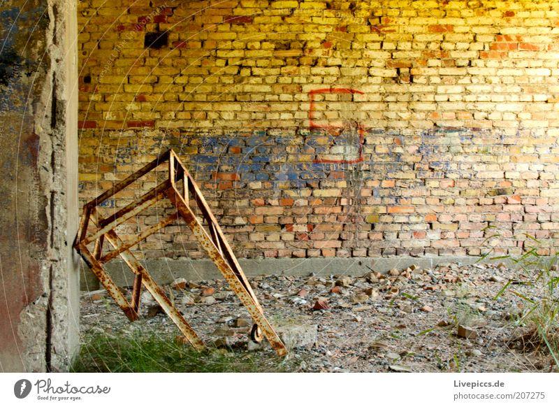 einsames Gestell gelb Wand Mauer braun Metall dreckig kaputt authentisch verfallen Verfall Rost Zerstörung gestellt Schrott Perspektive
