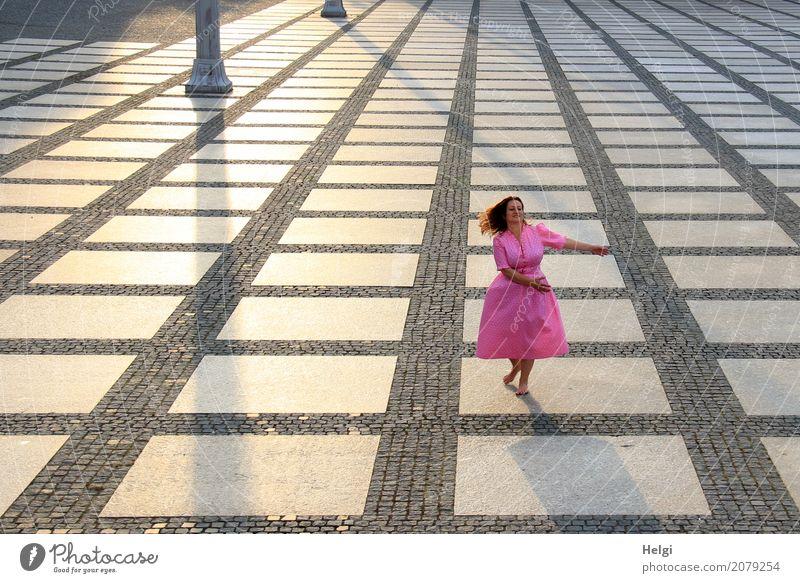 Frau mit langen brünetten wehenden Haaren und rosa Kleid tanzt barfuß auf einem großen gepflasterten Platz im Gegenlicht Mensch feminin Erwachsene 1 45-60 Jahre