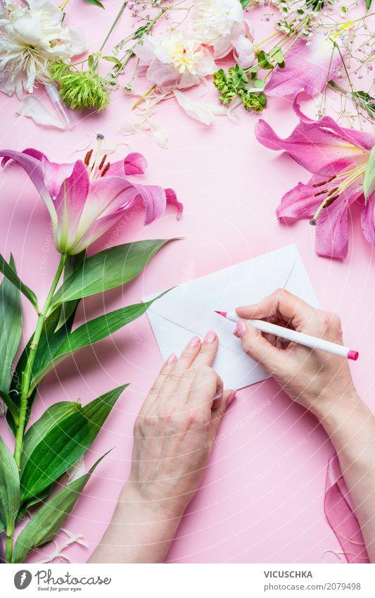 Weibliche Hände schreiben Grußkarte auf rosa Tisch mit Blumen Farbe Hand Blume Lifestyle Liebe feminin Stil Feste & Feiern Design rosa Häusliches Leben Dekoration & Verzierung Geburtstag Tisch Papier Hochzeit