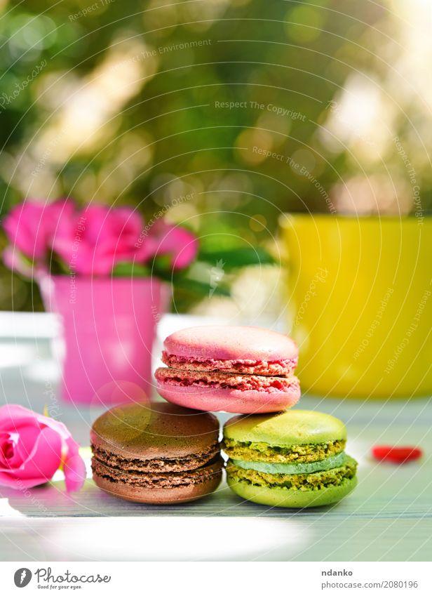 Drei bunte Makronen grün weiß Blume gelb Holz Lebensmittel rosa hell Tisch Kuchen Dessert Tasse Backwaren geschmackvoll backen Mandel