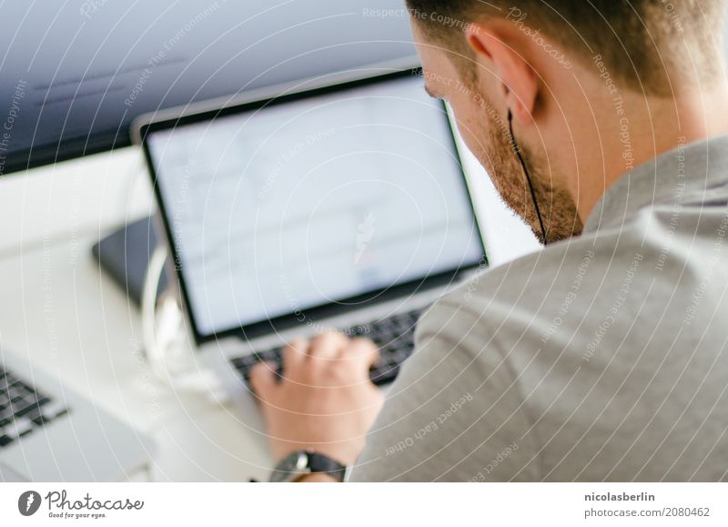 Junger Mann arbeitet am Laptop im Startup und hört Musik über in-ear Kopfhörer Berufsausbildung Azubi Praktikum lernen Student Prüfung & Examen
