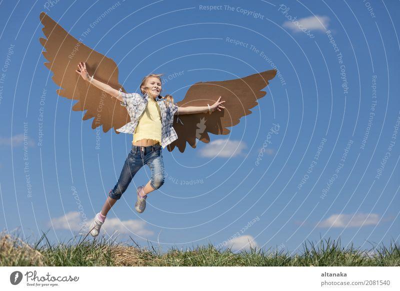 Kleines Mädchen, das tagsüber im Park mit Spielzeugflügeln aus Pappe spielt. Konzept des glücklichen Spiels. Kind hat Spaß im Freien. Bild vor dem Hintergrund des blauen Himmels.