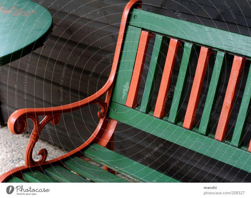 nimm Platz! Holz Streifen grün orange Bank Tisch Möbel Sitzgelegenheit Anschnitt Erholung Farbfoto Außenaufnahme Holztisch Holzbank Holzwand rot Menschenleer 1