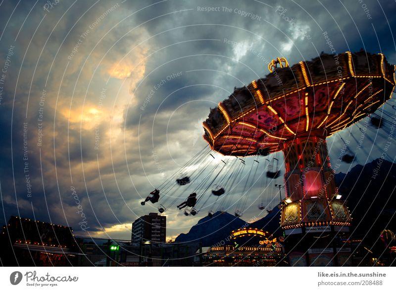 das Orchester spielt bis zum Schluß. Freude Jahrmarkt Kettenkarussell Karussell Ausflug Sommer Veranstaltung Wolken Gewitterwolken Sonnenlicht Unwetter fliegen