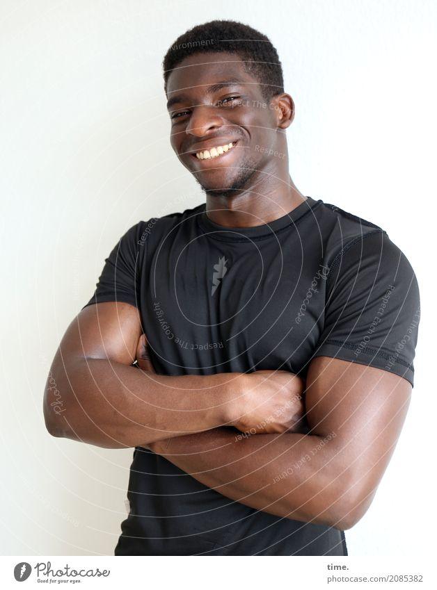 Kekeli maskulin Mann Erwachsene 1 Mensch T-Shirt schwarzhaarig kurzhaarig Dreitagebart beobachten festhalten lachen Blick Freundlichkeit Fröhlichkeit frisch