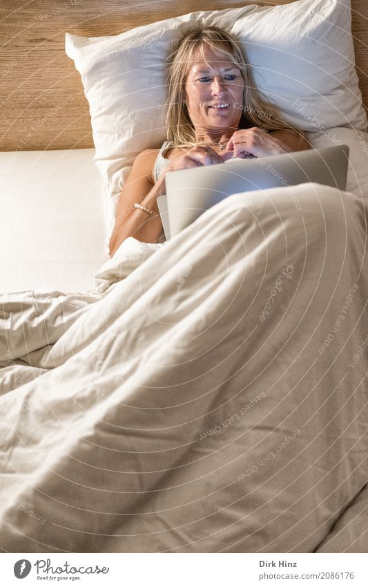 Frau liegt im Bett und schaut auf ein Notebook Lifestyle Freizeit & Hobby Mensch feminin Erwachsene 1 30-45 Jahre 45-60 Jahre authentisch Erotik Freundlichkeit