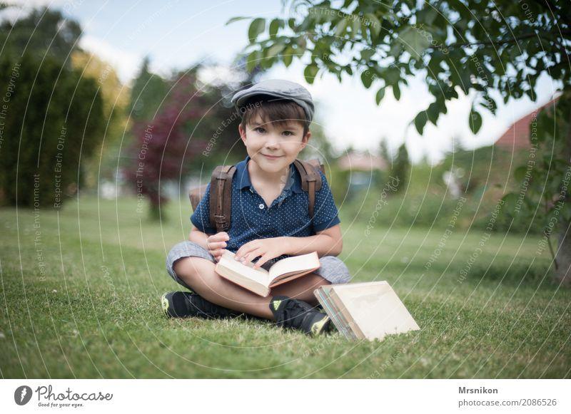 Schulanfang Mensch Kind Junge Kindheit Leben 1 3-8 Jahre Lächeln lernen sitzen Mütze Einschulung Buch antik Schulranzen Wiese Garten Außenaufnahme sommerlich