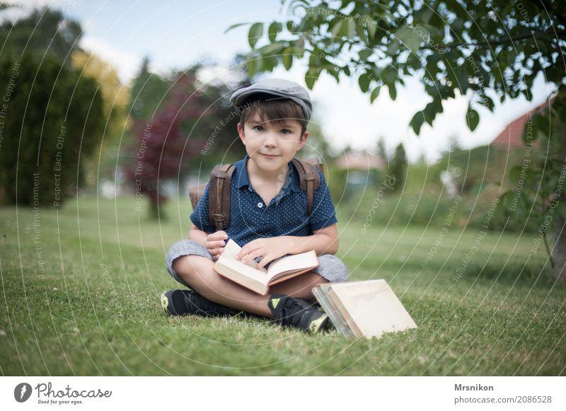 Schulanfang Mensch Kind Junge Kindheit Leben 1 3-8 Jahre Lächeln lernen sitzen brünett lesen Schule Einschulung Schulranzen antik Buch aufgeschlagen Farbfoto