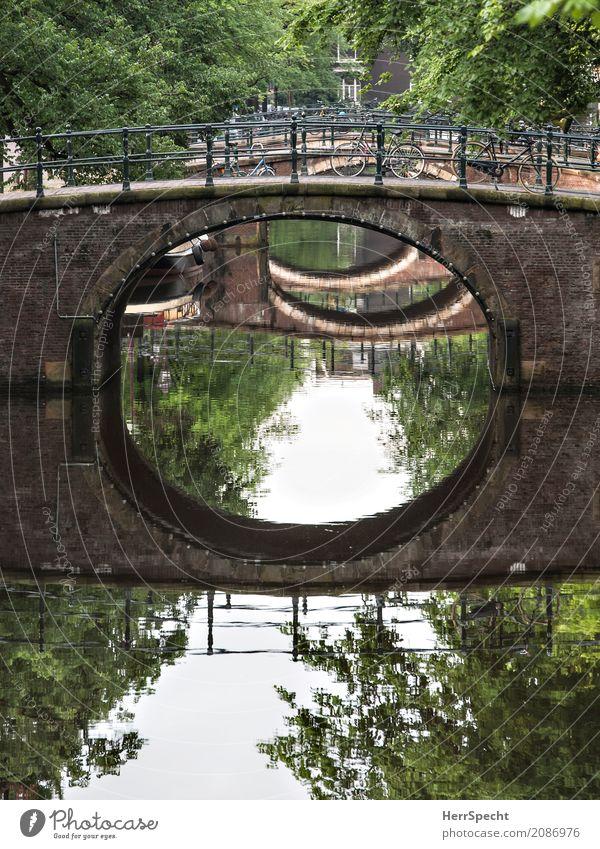 Dreibrückenkanal Amsterdam Stadtzentrum Brücke Bauwerk Verkehrswege Kanal Fahrrad ästhetisch rund Durchblick Perspektive Baum Allee historisch Farbfoto