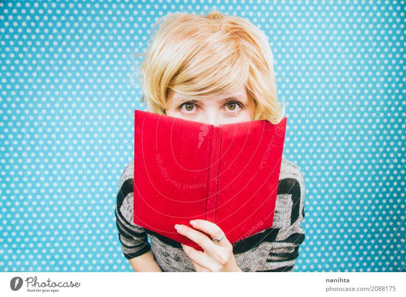 Junge blonde Frau von einem Buch bedeckt Mensch Jugendliche blau Junge Frau rot 18-30 Jahre Erwachsene gelb Lifestyle feminin Haare & Frisuren hell Kultur