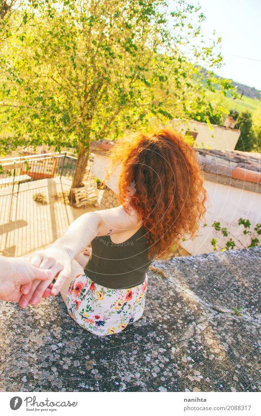 Hintere Ansicht einer jungen Rothaarigefrau, die eine Hand hält Mensch Ferien & Urlaub & Reisen Jugendliche Junge Frau Sommer grün Sonne rot Freude 18-30 Jahre