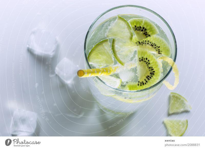 Erfrischendes kühles Erfrischungsgetränk mit Kiwi und Limette in einem Glas mit gelben Trinkhalm Getränk Limettenscheibe Zitronenschale Limone Trinkwasser