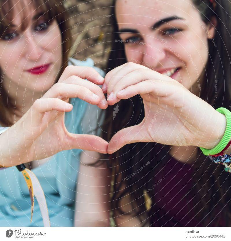 Zwei Freunde, die mit ihren Händen ein Herz schlagen lassen. Lifestyle Stil Freude Gesundheit Wellness harmonisch Mensch feminin Junge Frau Jugendliche