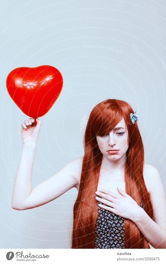 Die junge traurige Frau, die ein Herz hält, formte Ballon Valentinstag Mensch feminin Junge Frau Jugendliche 1 18-30 Jahre Erwachsene rothaarig langhaarig