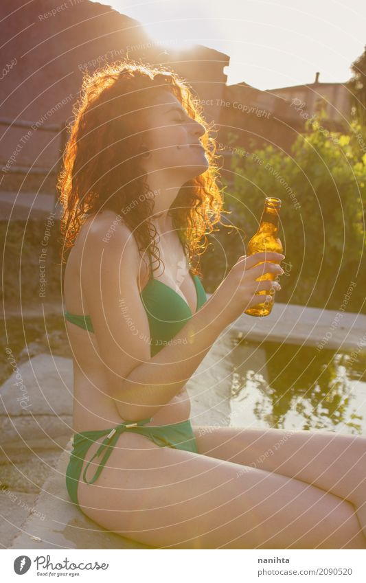 Junge Frau, die ein Bier in einem Pool am Sommer trinkt Mensch Jugendliche grün Wasser Sonne 18-30 Jahre Erwachsene Lifestyle feminin Party Feste & Feiern