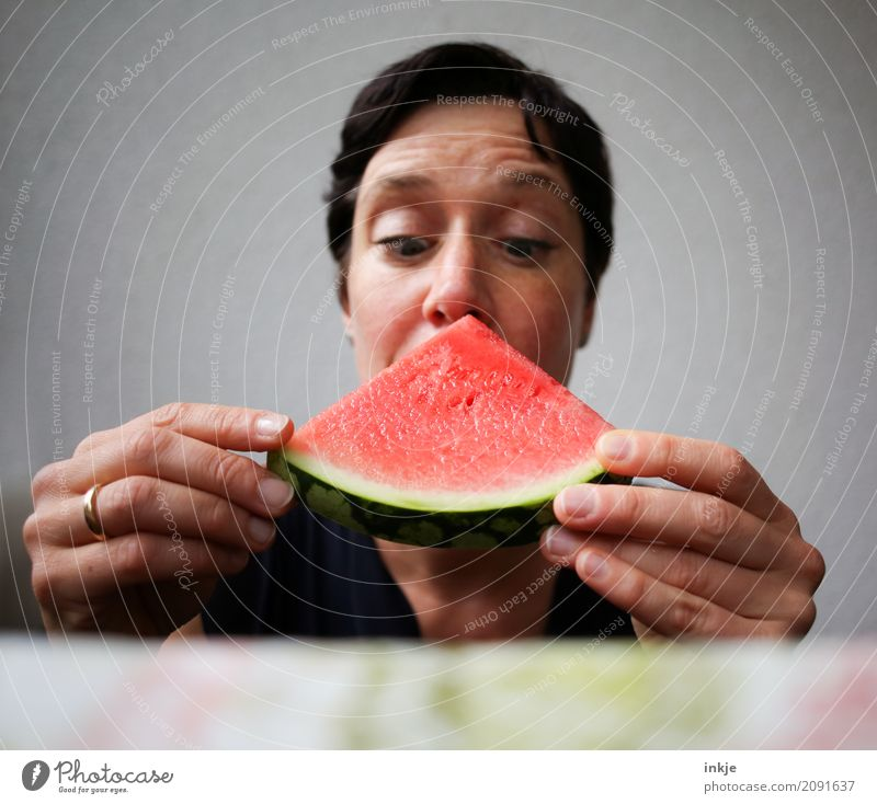 Not so young caucasian woman now almost biting in watermelon Frucht Wassermelone Melonen Ernährung Essen Vegetarische Ernährung Fingerfood Frau Erwachsene Leben