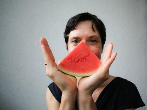 Frau mit Melonenstück vorm Gesicht Frucht Ernährung Bioprodukte Vegetarische Ernährung Fingerfood Lifestyle Stil Freude Freizeit & Hobby Erwachsene Leben Hand 1