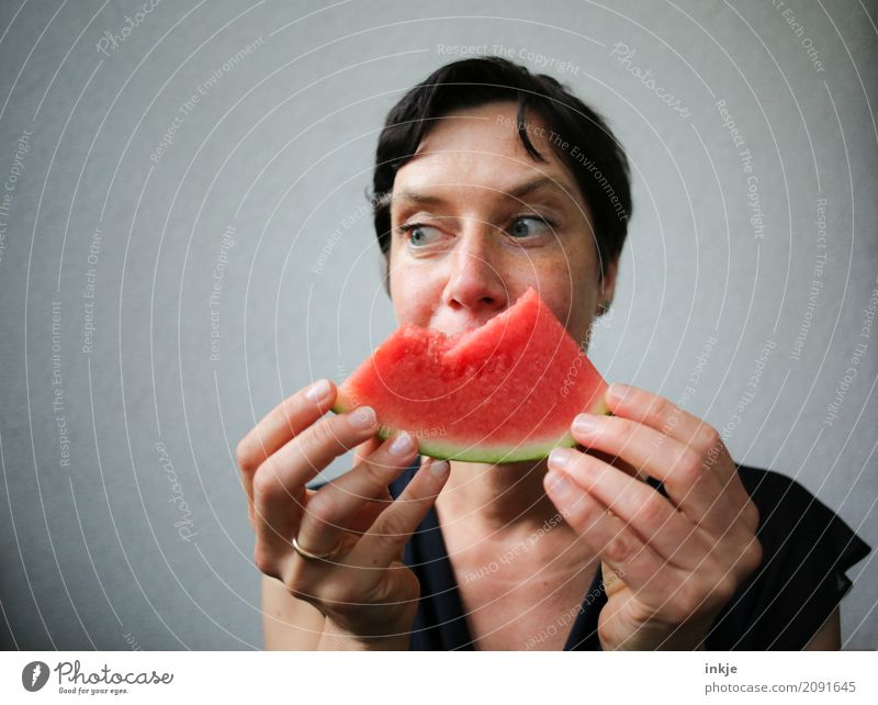 Not so young but happy Caucasian woman chewing watermelon Frucht Melonen Wassermelone Ernährung Essen Bioprodukte Vegetarische Ernährung Fingerfood Lifestyle