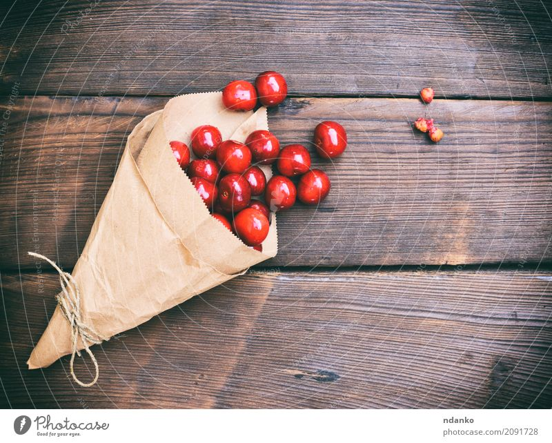 Reife rote Kirsche in einer Papiertüte Frucht Dessert Vegetarische Ernährung Holz Diät Essen frisch retro saftig Hintergrund Beeren Lebensmittel Ernte viele