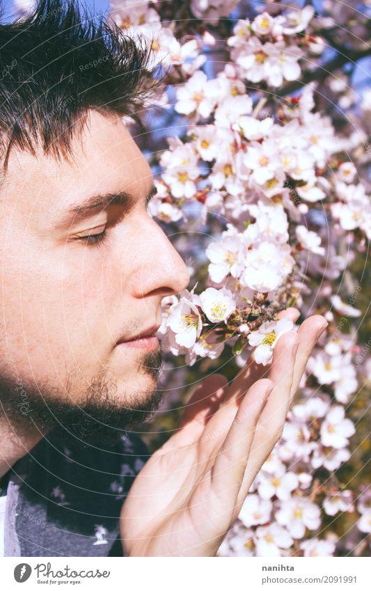 Junger Mann schnüffelt den Duft von Blumen Mensch Natur Jugendliche blau schön weiß Erholung ruhig 18-30 Jahre Erwachsene Umwelt Leben Lifestyle Frühling