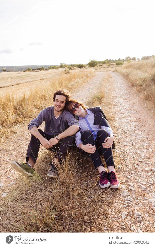 Junge Paare, die zusammen in einem ländlichen Weg sitzen Mensch Natur Jugendliche Junge Frau Junger Mann Erholung Freude 18-30 Jahre Erwachsene Leben Lifestyle