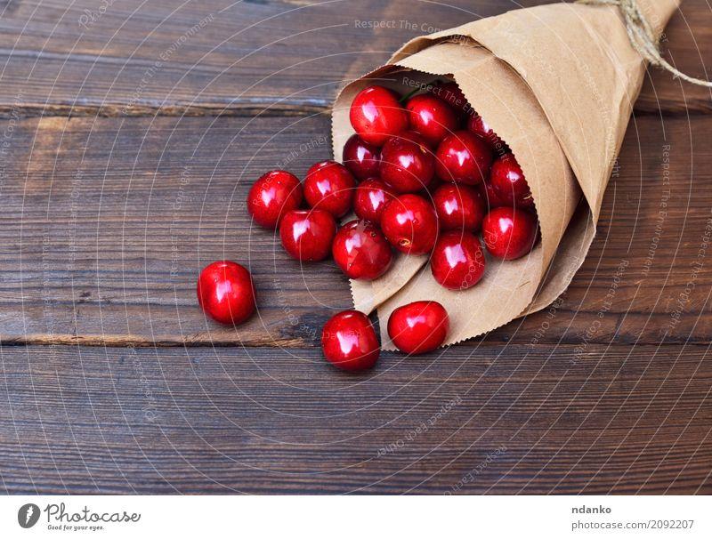 Rote reife Kirsche in einer Papiertüte Frucht Dessert Essen Vegetarische Ernährung Saft Sommer Tisch Natur Holz frisch natürlich oben retro saftig rot