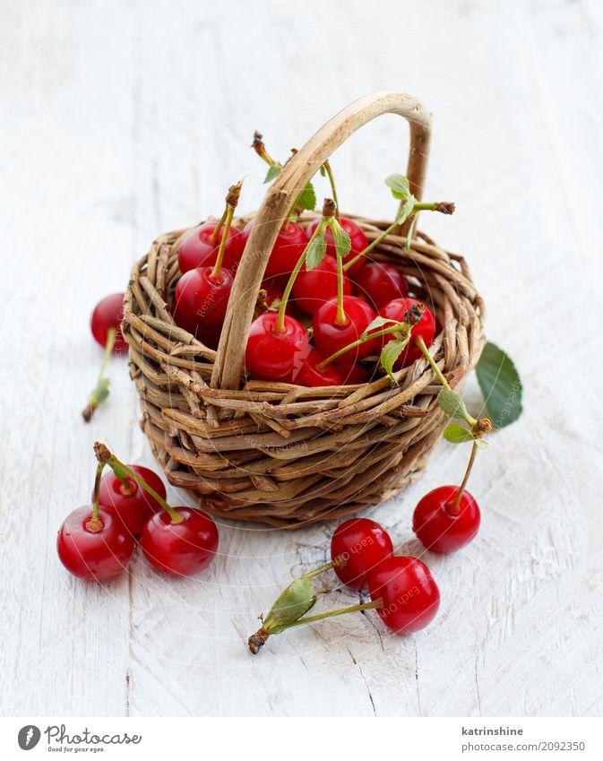 Frischer Sauerkirschen ina Korb auf einem Holztisch Frucht Vegetarische Ernährung Diät Sommer Tisch Blatt dunkel frisch lecker saftig sauer wild braun grün rot