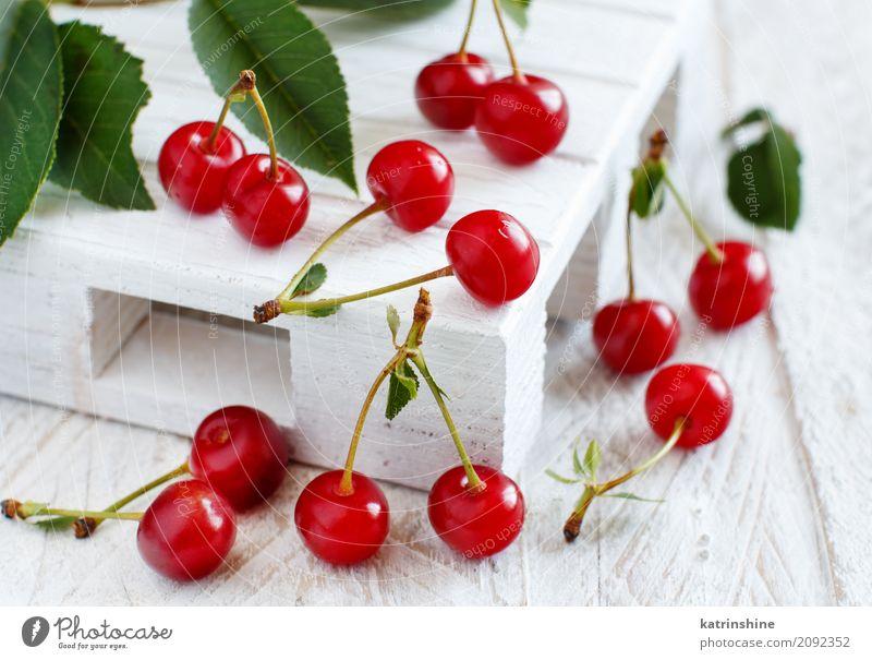 Frische Sauerkirschen auf einem weißen Holztisch Sommer grün rot Blatt dunkel braun wild Frucht frisch Tisch lecker Beeren Schalen & Schüsseln