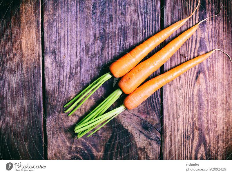 Drei frische Karotten Natur Pflanze grün Essen natürlich Holz Ernährung Tisch Gemüse Ernte Vegetarische Ernährung Diät Vitamin Salatbeilage Wurzel