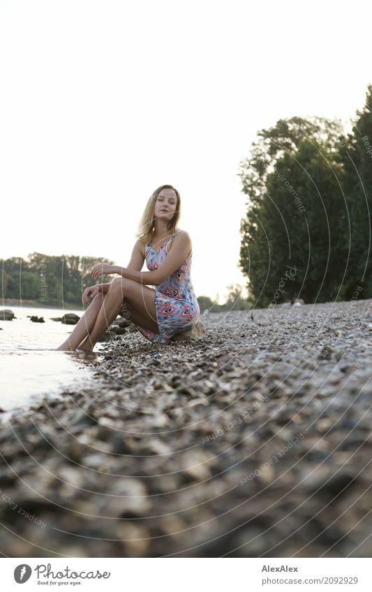 Junge Frau in Sommerkleid sitzt am Rheinufer mit dem Füßen im Fluss Wellness Erholung Ausflug Sommerurlaub Jugendliche Gesicht Beine 18-30 Jahre Erwachsene