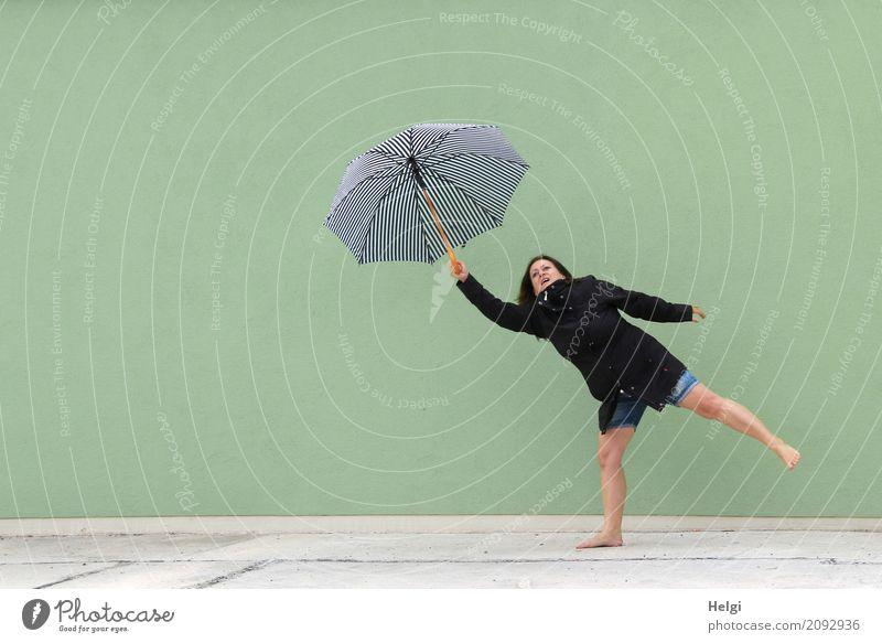 Frau mit schwarzer Jacke und kurzer Jeans steht barfuß auf einem Bein vor einer hellgrünen Wand und hält mit einem Arm einen Schirm hoch Mensch feminin