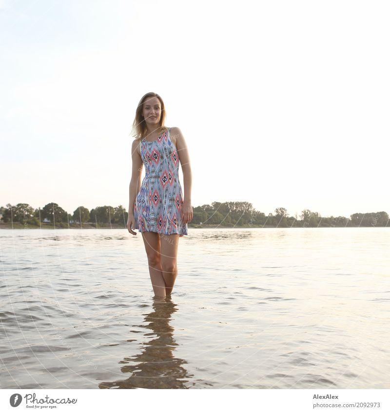 Gegenlichtportrait einer jungen Frau im Sommerkleid die mit den Füßen im Wasser steht Lifestyle Freude schön Körper Wohlgefühl Ausflug Junge Frau Jugendliche