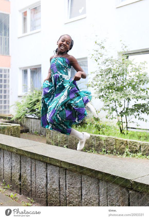 Gloria Fitness Sport-Training Mädchen 1 Mensch Haus Mauer Wand Kleid schwarzhaarig langhaarig lachen springen Fröhlichkeit Glück schön Freude Zufriedenheit