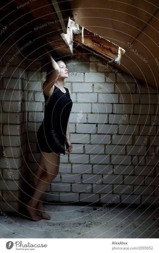 Junge Frau steht auf dem Dachboden barfuß vor dem Oberlicht Dachgebälk Backsteinwand Jugendliche Beine Fuß 18-30 Jahre Erwachsene Kleid Barfuß brünett