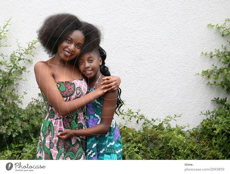 Arabella und Gloria feminin Mädchen Frau Erwachsene Schwester 2 Mensch Grünpflanze Mauer Wand Kleid Schmuck schwarzhaarig brünett langhaarig Locken Afro-Look